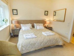 A bed or beds in a room at Brooksides Byre Durham Country Cottage