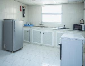 A kitchen or kitchenette at Nuzha Hotel Apartments