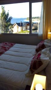 Una cama o camas en una habitación de Departamento con vista al lago en Bariloche.