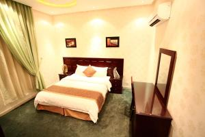 A bed or beds in a room at Rest Night Hotel Suites- AL Falah