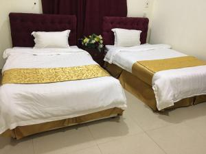A bed or beds in a room at Layal Wardiyah Furnished Units