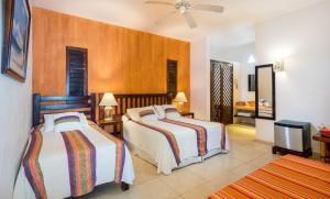 A bed or beds in a room at Villas El Encanto Cozumel