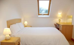 A bed or beds in a room at Burren Way Cottages