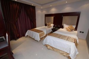 A bed or beds in a room at Raoum Inn Hail