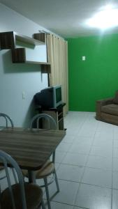 A television and/or entertainment center at Apartamento Enseada Residence