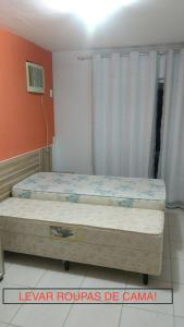 A bed or beds in a room at Apartamento Enseada Residence