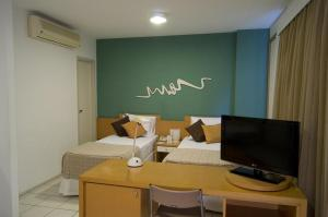 A television and/or entertainment center at Praia do Canto Apart Hotel