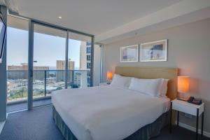 A bed or beds in a room at Hilton Surfers Paradise Residences