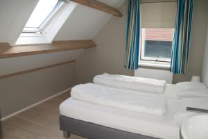 A bed or beds in a room at Vakantiehuizen Hofstede Elzenoord