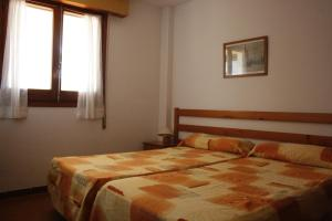 A bed or beds in a room at Apartamentos Arlanza - Only Adults