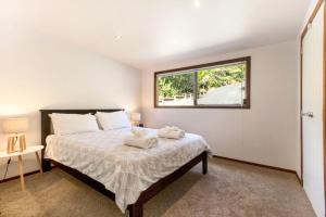 A bed or beds in a room at Karaka Sanctuary