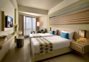 A bed or beds in a room at Citadines Kuta Beach Bali