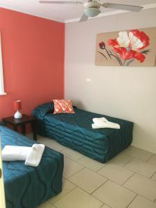 A bed or beds in a room at Beachlander Holiday Apartments