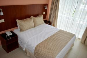 A bed or beds in a room at Aparthotel Premium Suites Equipetrol