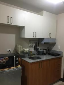 A kitchen or kitchenette at Ness Apartment at Manhattan Heights Cubao