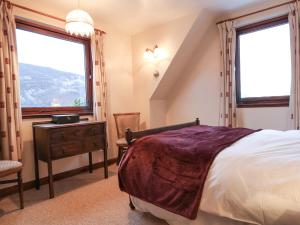 A bed or beds in a room at Carnoch Farm Cottage, Beauly