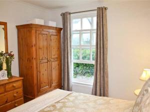 A bed or beds in a room at Crown Cottage, Tenby