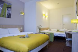 A bed or beds in a room at Aparthotel Adagio Access Bruxelles Europe Aparthotel