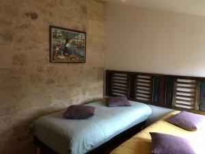 Un ou plusieurs lits dans un hébergement de l'établissement Gite dans un chai à vin