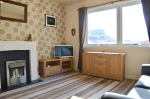 A television and/or entertainment centre at Crags View Apartment On The Royal Mile