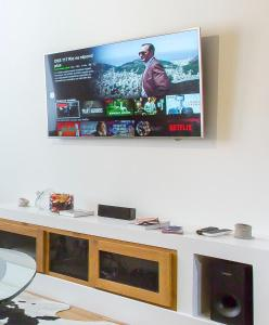 A television and/or entertainment center at HAMAC Suites Lyon Boissac