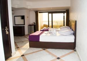 A bed or beds in a room at Galaxy Royal Suites Hotel