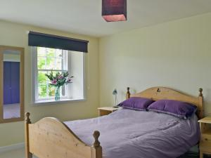 A bed or beds in a room at Kinnettas Cottage