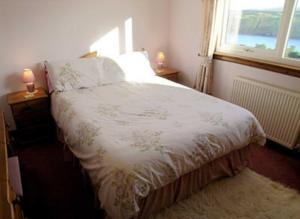 A bed or beds in a room at Distillery Croft Cottage