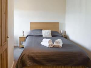 A bed or beds in a room at Cor Cottage