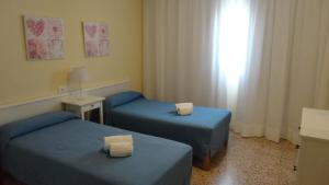 A bed or beds in a room at Apartamentos Cala Llonga