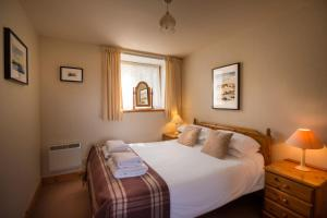 A bed or beds in a room at Carden Holiday Cottages