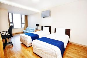 A bed or beds in a room at Hyundai Residence