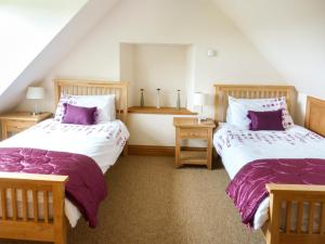 A bed or beds in a room at Drumfad Cottage, Newton Stewart