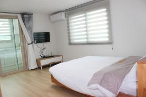 A bed or beds in a room at Jeju Aria Pension