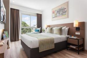 A bed or beds in a room at Citadines Regency Saigon