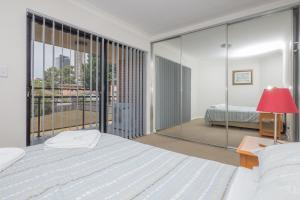 A bed or beds in a room at Parkside Apartments Parramatta
