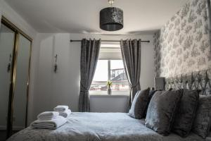 A bed or beds in a room at No.27 Ayr Beach - Coorie Doon