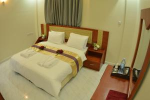 A bed or beds in a room at Bahla Jewel Hotel Apartments