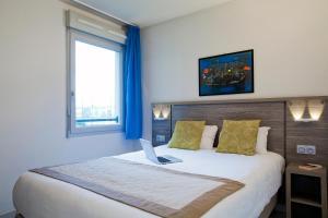 Un ou plusieurs lits dans un hébergement de l'établissement Séjours & Affaires Clermont Ferrand Park République
