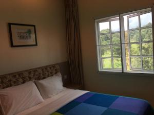 A bed or beds in a room at CH Green Stay Resort Apartment