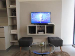 Una televisión o centro de entretenimiento en Santiago Central Suites / San Martin