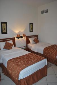 A bed or beds in a room at Al Deyafa Hotel Apartments