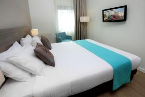 A bed or beds in a room at Citadines Toison d'Or Brussels Aparthotel