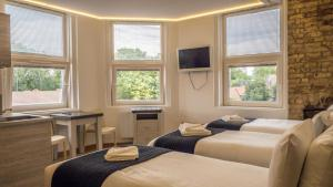 A bed or beds in a room at London Stay Apartments