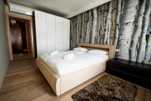 A bed or beds in a room at Angel City Center Krakow Aparthotel