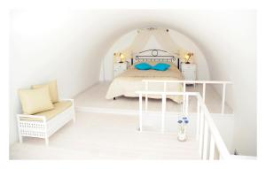 A bed or beds in a room at Reverie Santorini Hotel