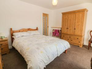 A bed or beds in a room at Fron Olau, Pwllheli