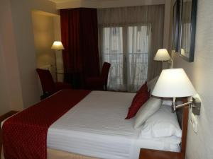 A bed or beds in a room at Aparto-Hotel Rosales