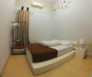 A bed or beds in a room at Rumah Ayin Homestay Near Airport