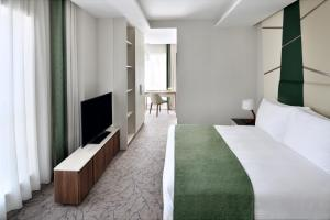 A bed or beds in a room at Mövenpick Hotel Apartments Downtown Dubai